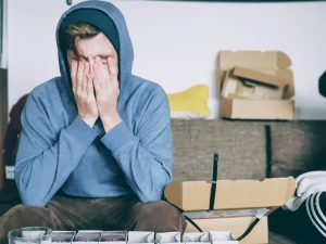 Overwhelmed man sitting with his head in his hands | How To Manage Stress in Your Schedule