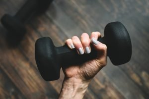 Woman holding a black dumbbell