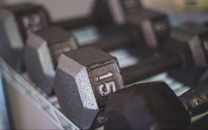 Black dumbbells on a rack | 15-Minute Arm Workout