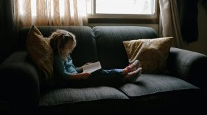 Young child reading on the couch | Staycation Ideas