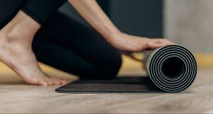 Woman unrolling yoga mat | Home Back Workout